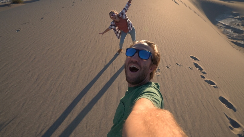 Couple traveling takes selfie picture on sand dunes at sunset. Young couple taking selfies in wester USA. People travel concept. | Shutterstock HD Video #1032515807