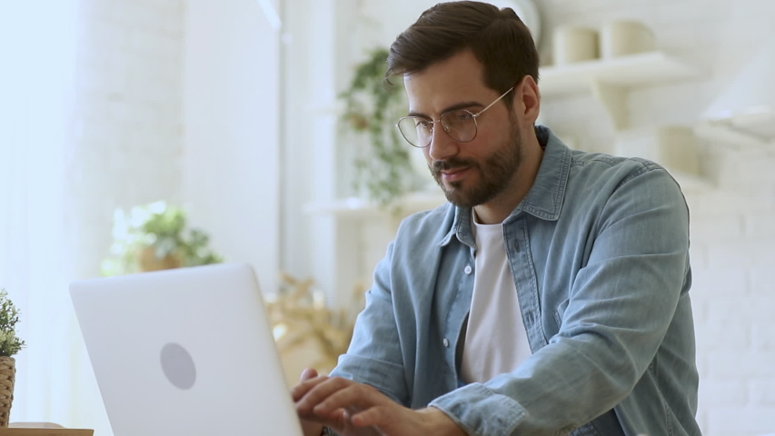 Young man freelancer student using laptop studying online working from home in internet, smiling focused millennial guy typing on computer surfing web looking at screen enjoying distant job