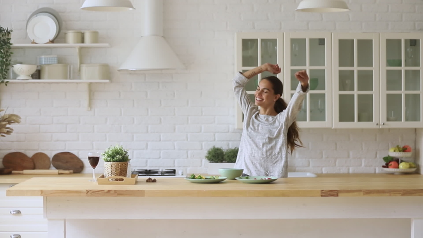 Carefree happy young woman housewife dancing alone cooking meal in modern kitchen, funny cheerful active pretty girl preparing food healthy dinner vegetable salad at home having fun listening music | Shutterstock HD Video #1032517217