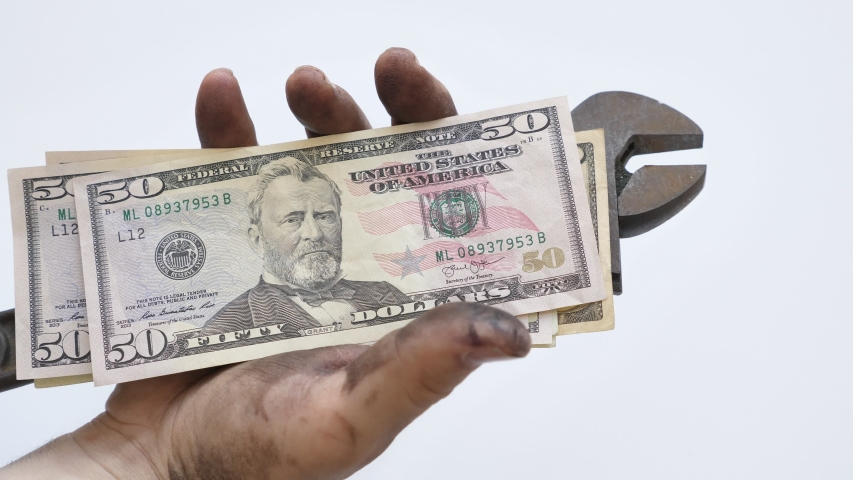 Technician with dirty hands holding wrench and USD bills in his hand Isolated over white background | Shutterstock HD Video #1032522257