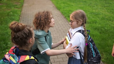 Group of teenagers are pushing and insulting a schoolgirl. Adolescent violence problem. Bullying among adolescents and schoolchildren. Physical violence