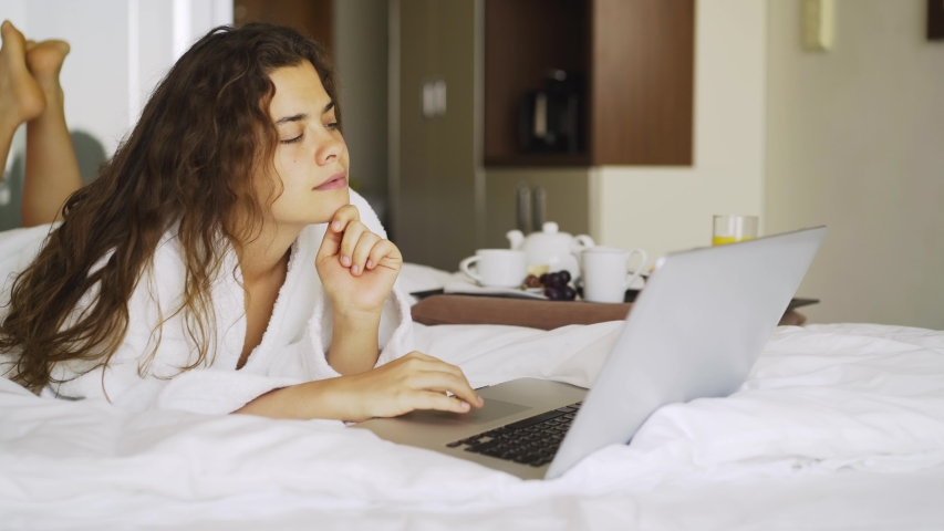 Woman have breakfast in modern hotel apartment. Window light portrait young girl in bathrobe lying on bed using laptop for work. Out of focus tray with meal, juice, plate, teapot on background | Shutterstock HD Video #1032560597