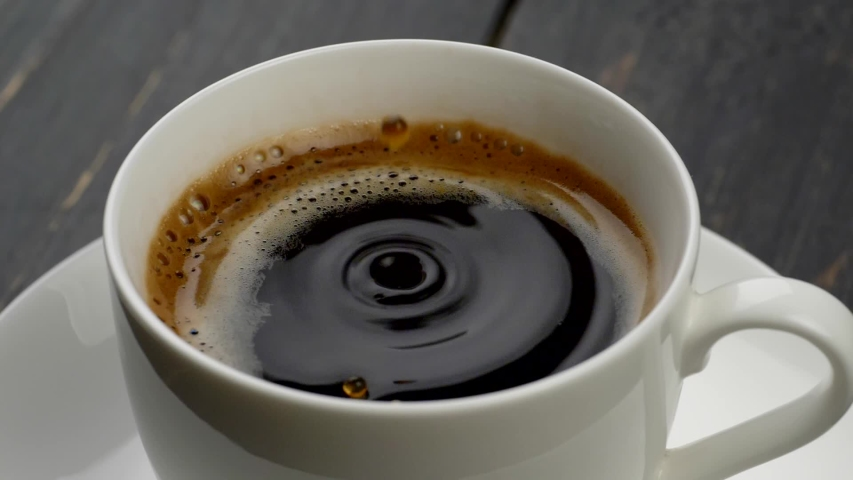 Cup of coffee close-up. Circle shaped coffee water drops falling into black, orange foamed, coffee in a white cup, put on a white saucer on a wooden table. Slow motion shot | Shutterstock HD Video #1032732227