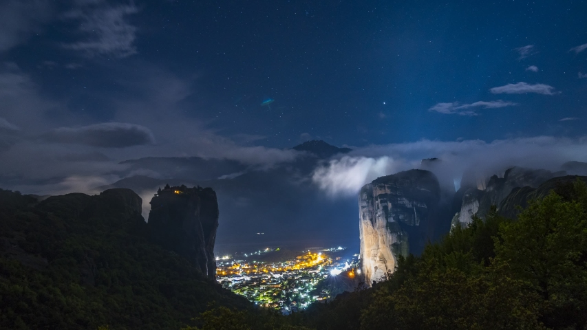 Timelapse of the village of Kalambaka in the famous Greek tourist spot Meteora in Greece at night. Very beautiful scenic view. Clouds and stars on the background of rocks