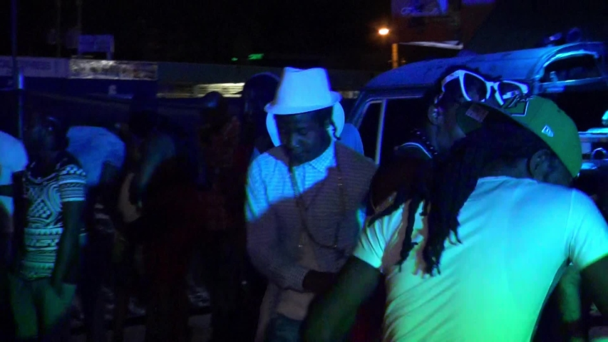 KINGSTON, JAMAICA - CIRCA JUNE 2017 : Scenery of outdoor street night club. Man and woman enjoying dance, popular night life for many Jamaican people. Reggae and hip hop music are played by DJ. #1032757517