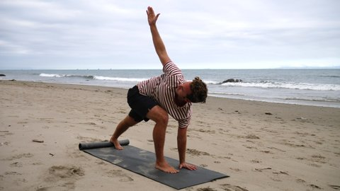 A man doing yoga on the beach over the ocean waves crashing on the California shore in slow motion.