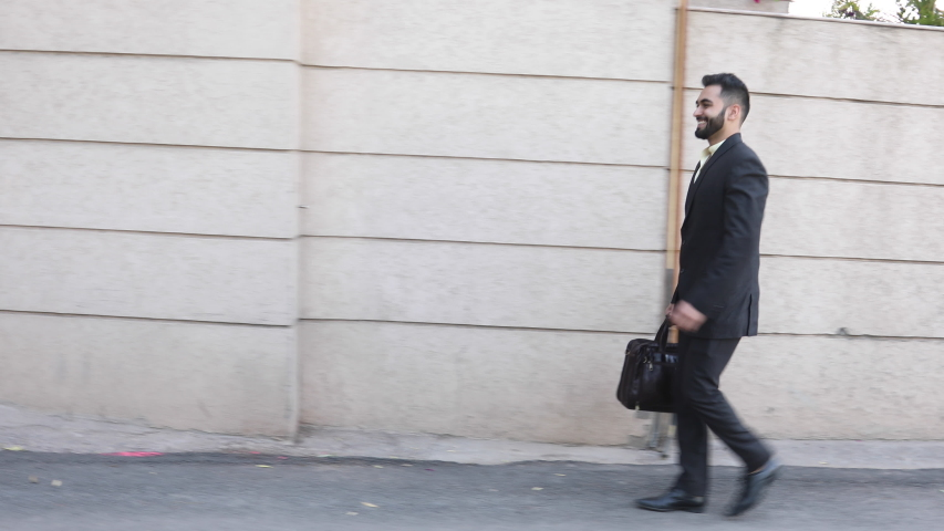 Portrait of a happy businessman walking outdoors in the Street  #1032806387