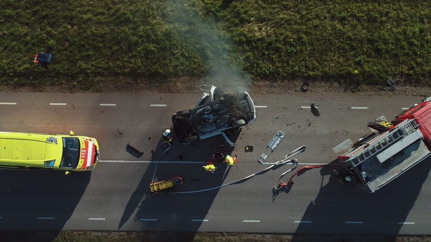 Aerial View: Rescue Team of Firefighters and Paramedics Work on a Car Crash Traffic Accident Scene. Preparing Equipment, First Aid Help. Saving Injured and Trapped People from the Burning Vehicle | Shutterstock HD Video #1032835907