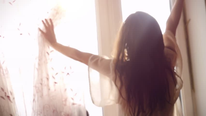 Slowmotion of young attractive sexy woman with slender body and her Maine Coon cat opening curtain and looking out the window at the sunrise on a sunny morning