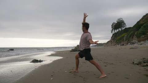 A man doing a yoga pose into a handstand on the beach with ocean waves in Santa Barbara, California SLOW MOTION.