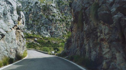 Point of view shot of a driver in his car driving along a straight section of Serra de Tramuntana Road towards Sa Calobra in Majorca, overtaking a cyclist to his right.