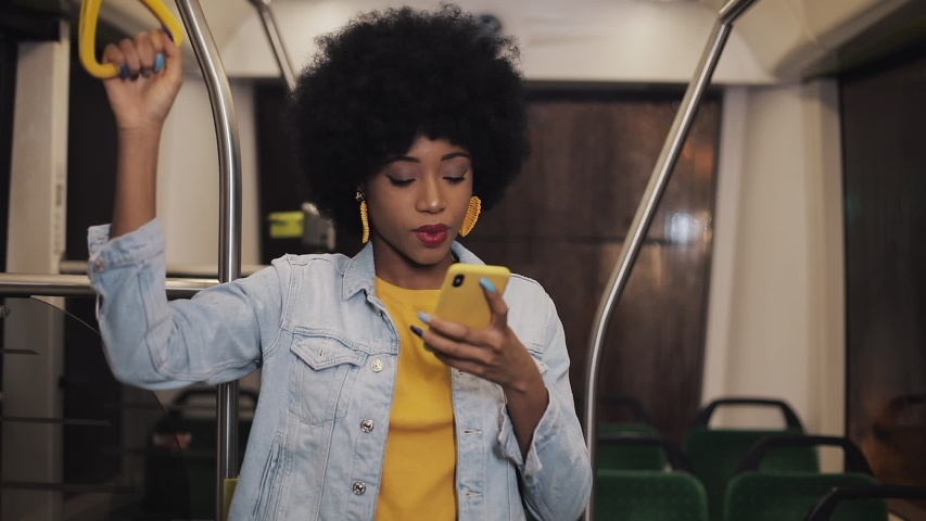 Happy afro businesswoman cheering celebrating looking at smartphone. Young urban professional successful business woman receiving good news riding in public transport.