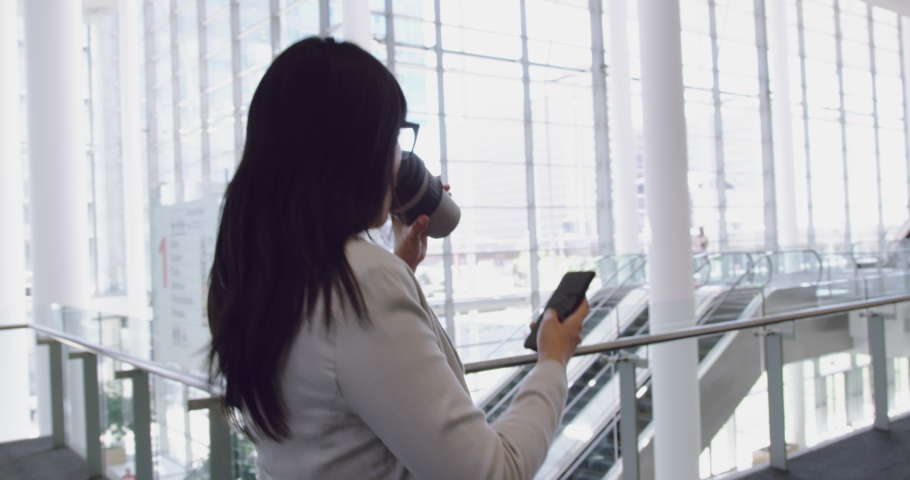 Side view of Asian Businesswoman talking on mobile phone and walking in the lobby at office. She is drinking coffee 4k   Shutterstock HD Video #1032973787