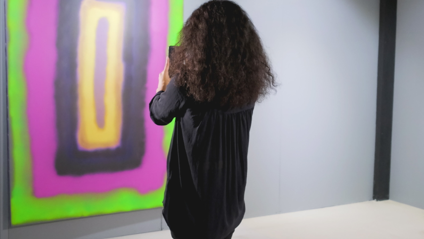 Young woman is photographing abstract artwork in modern gallery. She is using camera of her gadget, focussing on canvas