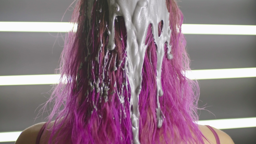 Paint flows down on hair of the fashionable girl and it smears it on hair | Shutterstock HD Video #1033109687