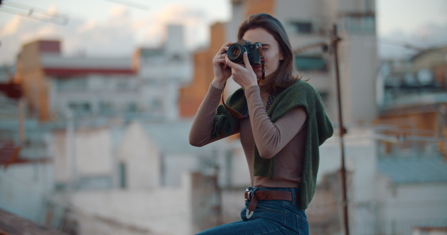 Attractive young girl in hipster outfit using retro camera on the rooftop in the old part of the city of Barcelona looking with friendly smile admiring the city, People Lifestyle Hobby, Slow Motion   Shutterstock HD Video #1033111007