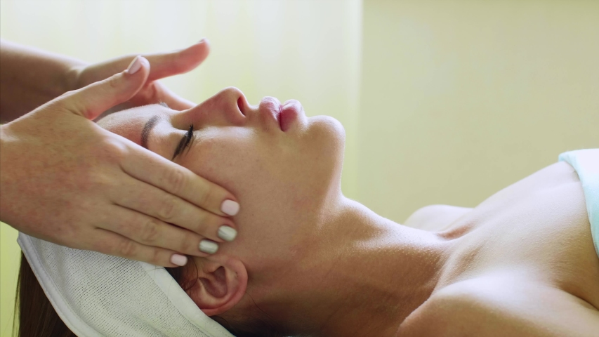 Beauty treatment in spa salon. Portrait of young woman is relaxing with close eyes on facial massage in cosmetology center, side view. Massage on face, neck and chest in slow motion. | Shutterstock HD Video #1033189217