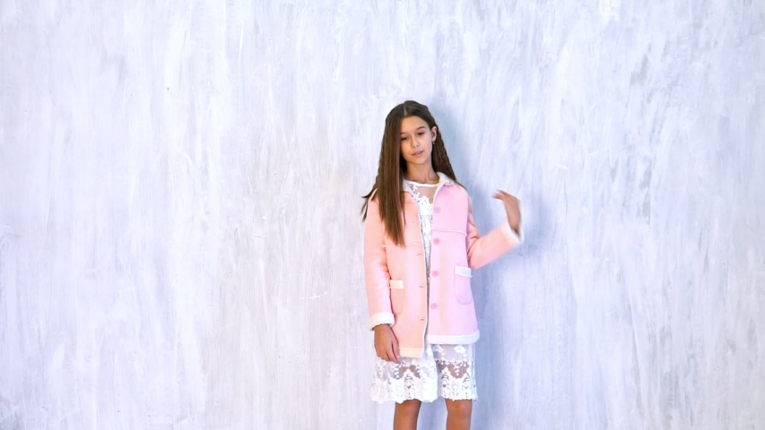 Beautiful fashionable girl poses on a gray background | Shutterstock HD Video #1033248857
