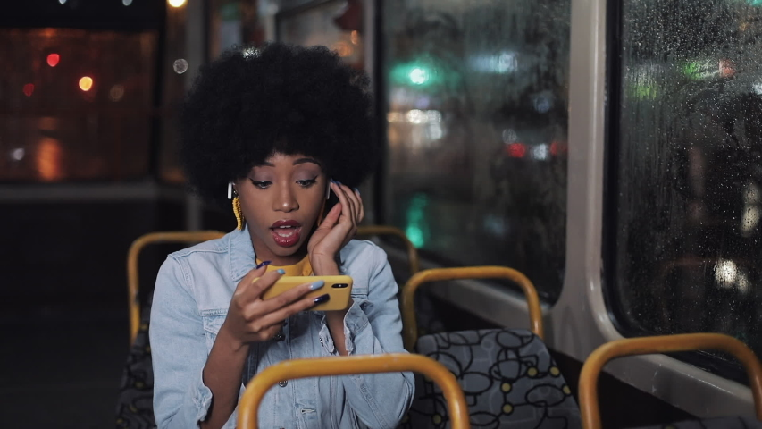 Smiling young african american woman watching funny video on the smartphone riding in the public transport. Night time. Close-up. City lights background. | Shutterstock HD Video #1033268927