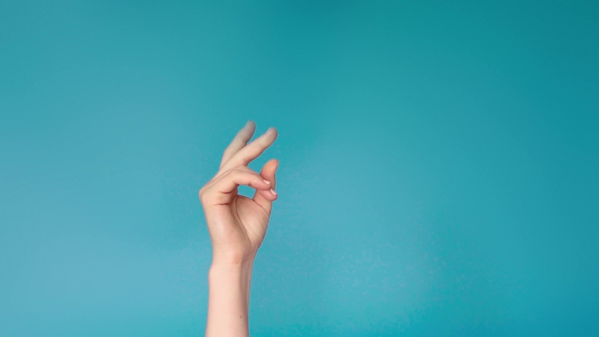 Woman hand snaps her fingers over blue background. Female hand with snapping fingers on blue screen background. Snapping fingers of caucasian woman hand 4k | Shutterstock HD Video #1033335737