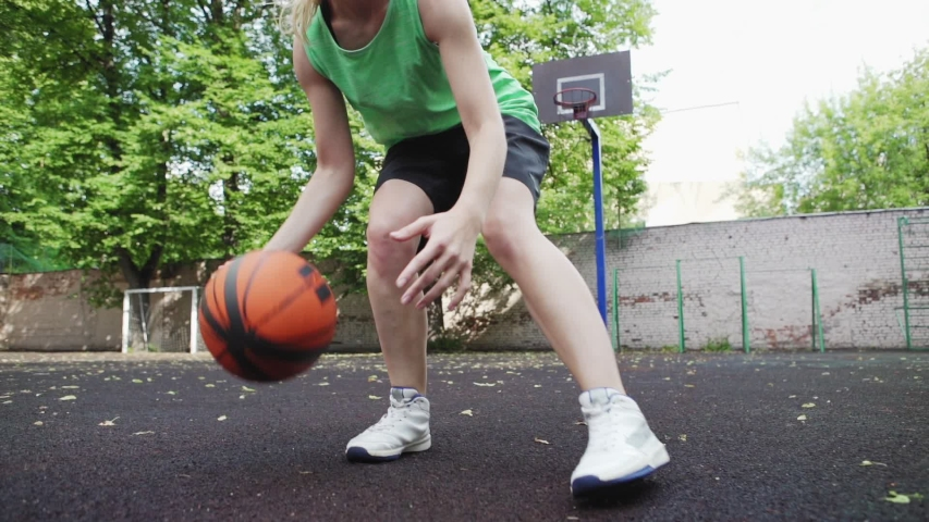 Female student handling ball skillfully while practicing basketball drill exercise on outdoor urban court, handheld shaky camera slow motion shot | Shutterstock HD Video #1033384367