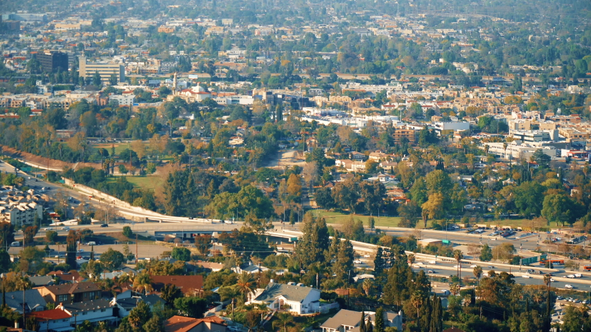 View of the city with green spaces. Green mountains in the city with a lot of beautiful trees. Freeway aerial view. Breathtaking look at busy city from the hills. Overlook with slow motion.