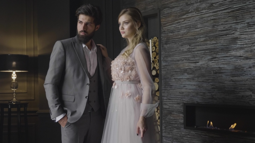 Slow motion elegant blond lady in nice dress and bearded man in grey suit stand at fireplace in dim room | Shutterstock HD Video #1033402967
