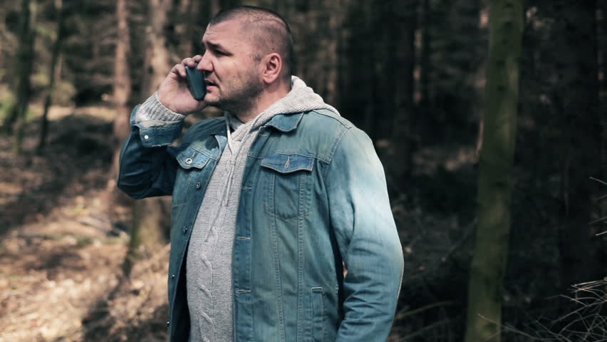 Young man talking on cellphone and looking for direction in forest  | Shutterstock HD Video #10335557
