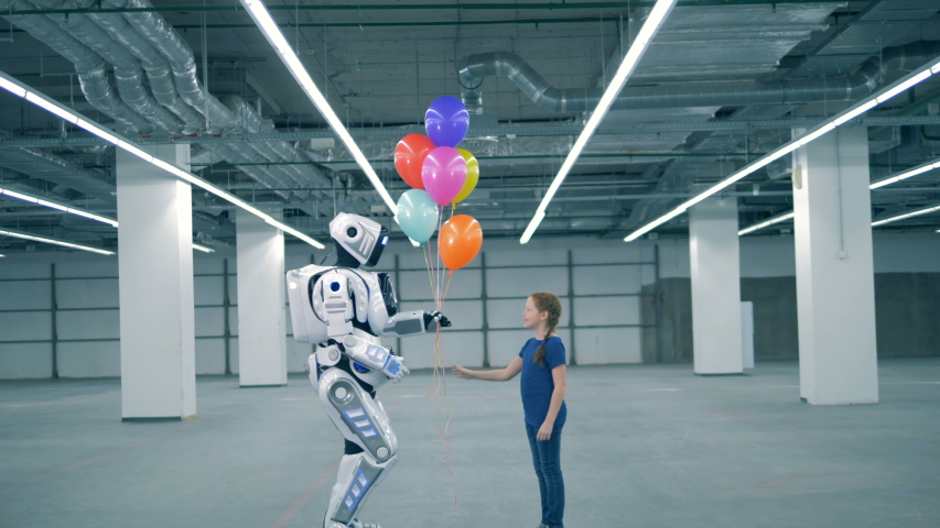 Little girl gives balloons to a droid, side view. School kid, education, science class concept. | Shutterstock HD Video #1033569737