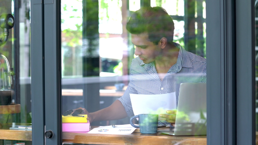 4K Medium shot young adult asian man college university economics student sitting in coffee shop doing economics business research with computer laptop outdoors. Hard work business education concept. | Shutterstock HD Video #1033610027