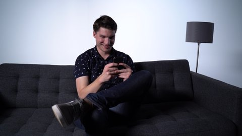 Slow Pan of Caucasian Man on Phone on Couch Laughing at Funny Meme
