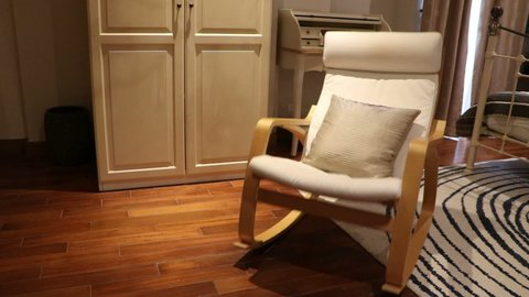 Wooden rocking chair with pillow in bedroom swing (fast to slow) by nobody in there