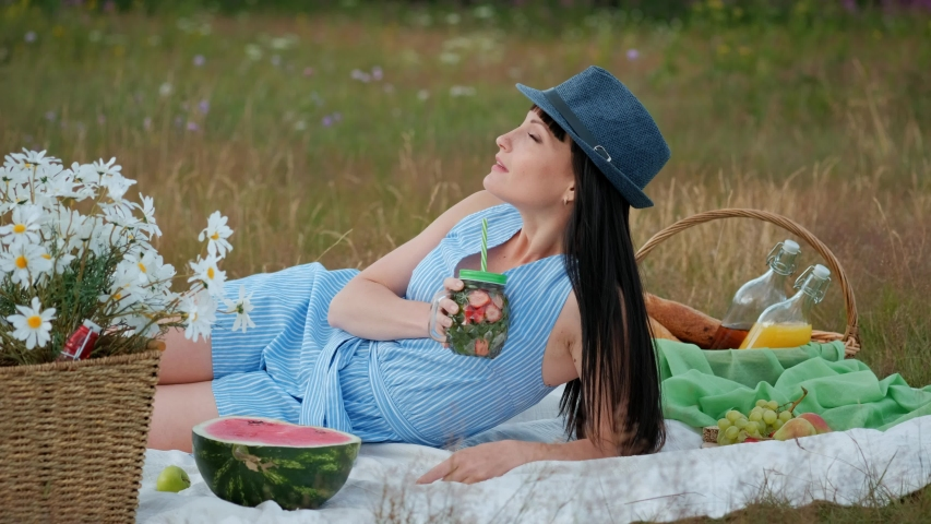 A young beautiful woman in a hat and dress is drinking lemonade from a can while sitting on a plaid on the green grass. Picnic basket, a bouquet of daisies, watermelon. The concept of giving away in | Shutterstock HD Video #1033706027