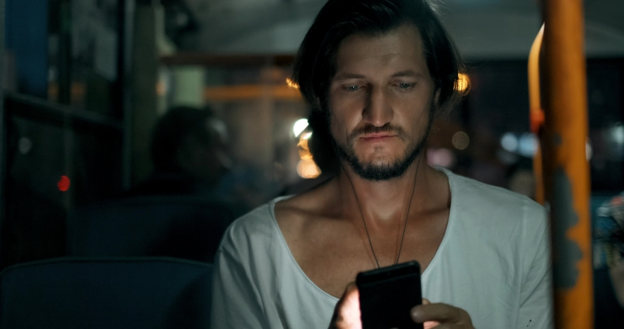 Young man holds smartphone while traveling by bus at night. Bearded male in headphones with phone, touches screen with fingers and looks out window | Shutterstock HD Video #1033729367