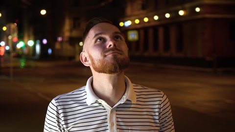 Handsome man with beard look up and then in camera. Dressed in striped polo shirt and stand on street at night.