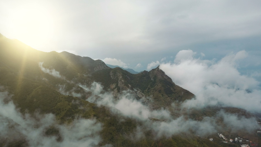 Epic morning Flight over Beautiful mountains and clouds at sunrise on Tenerife, Canary Islands. Water drops fall from the sky. Aerial view of nice rainy morning in Mountains.