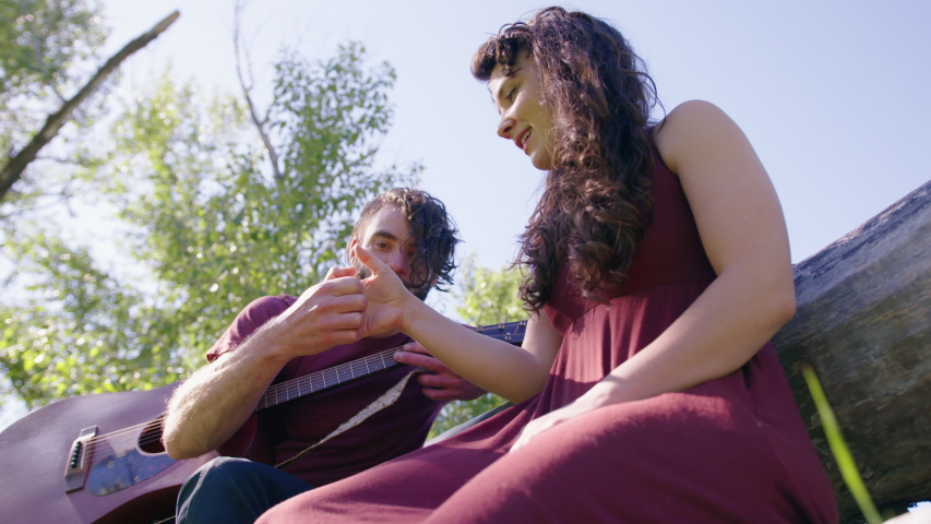 Slow motion low angle handheld of a millennial caucasian couple playing thumb wars in a park on a fallen tree, male holding his guitar | Shutterstock HD Video #1033849217