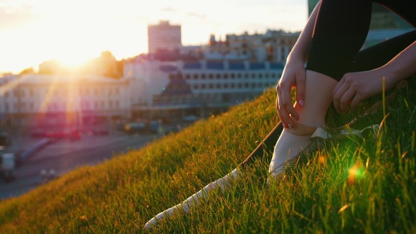 Young attractive ballerina takes off her pointe shoes sitting on a green hill in the middle of the city. | Shutterstock HD Video #1033908347
