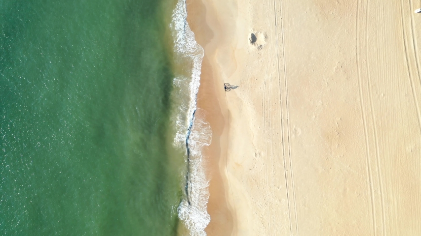 Bicyclist riding along golden beach (Virginia Beach). Distant aerial view.