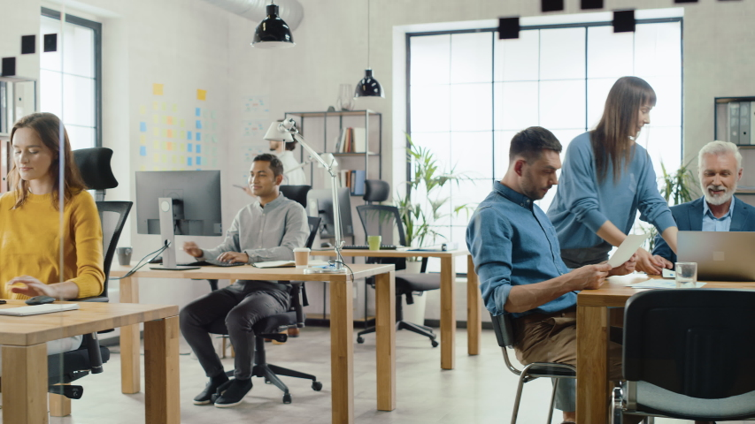 In the Stylish Modern Office: Diverse Group of Enthusiastic Business Marketing Professionals Use Computers, Have Meetings, Discussing Project Ideas, Brainstorming Startup Company Strategy | Shutterstock HD Video #1033983047