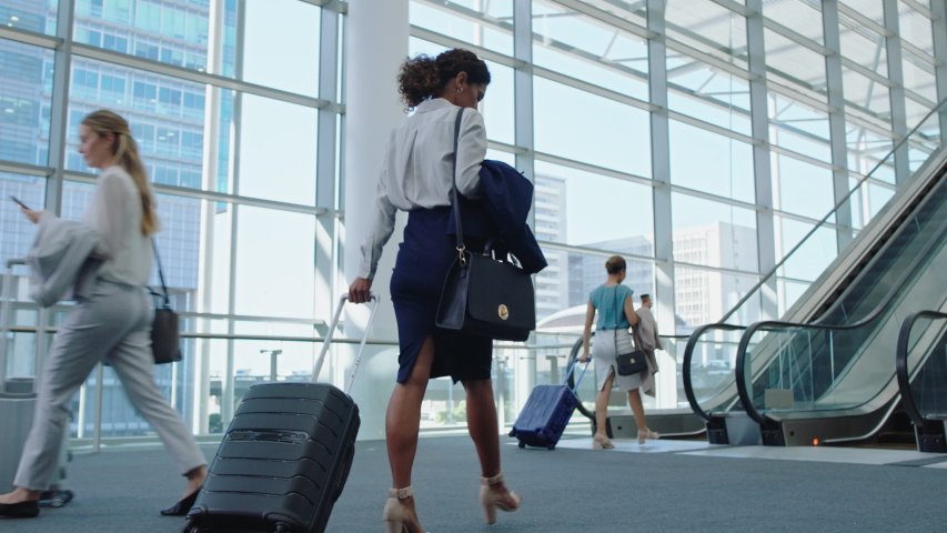 Business woman traveler walking in airport with trolly bag going up escalator female executive traveling international for business trip checking messages on smartphone 4k | Shutterstock HD Video #1034047667