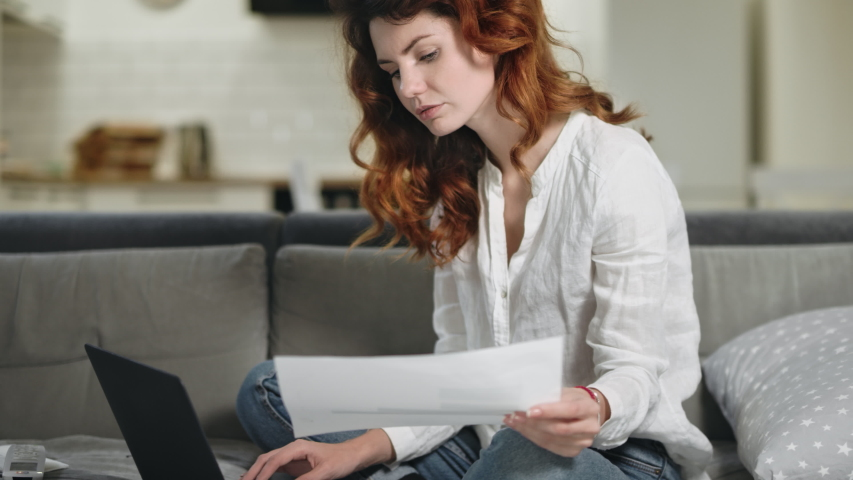 Focused woman working laptop at home. Serious business woman working with documents at remote workplace. Pretty girl checking paper at living room. | Shutterstock HD Video #1034233157