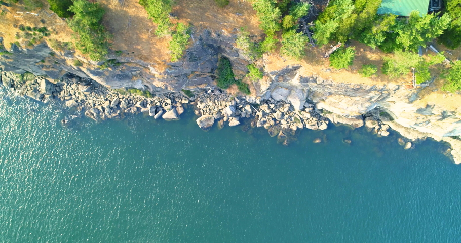 Aerial drone shot begins looking straight down a rocky cliff at the boulders and ocean shoreline below then travels inland over a forest to reveal a road in the trees. | Shutterstock HD Video #1034269217