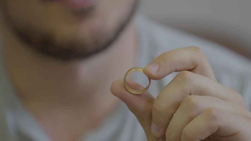 Portrait of unrecognized bearded man holding golden wedding ring sitting at home. The guy going to make a proposition for his girlfriend or remembers the pleasant moments of family life. | Shutterstock HD Video #1034277317