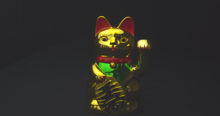 Closeup shoot of golden shiny chinese lucky cat waving a paw with background isolated on black | Shutterstock HD Video #1034338187