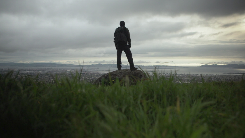 A photographer proudly stands on a cliff with an incredible view of the city and sunset on a beautiful cloudy evening.  Shot in 4K UHD resolution.   Shutterstock HD Video #1034396177