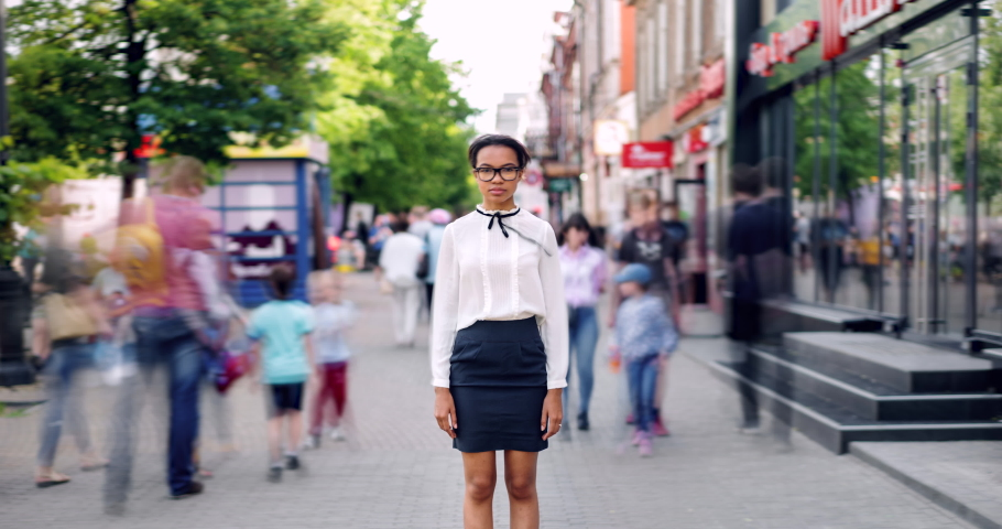 Zoom in time lapse of pretty African American lady standing in busy street on summer day looking at camera with serious face. Modern lifestyle, people and youth concept.