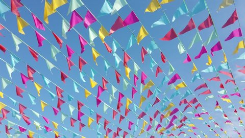 4k footage colorful party bunting flag waving against blue sky during bright sunny day.