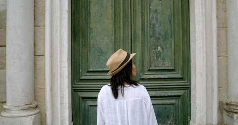 Woman in front of massive antique door from behind in fedora travelling abroad lost standing in Italian square looking at map in Venice Italy