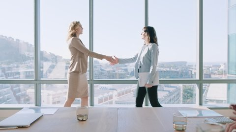 business women shaking hands in boardroom meeting successful corporate partnership deal with handshake colleagues clapping hands welcoming opportunity for cooperation in office 4k